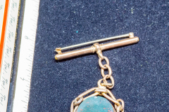 Helen Paddle jewelry gold lapel pin with reversing stone pendant red and green Patti giving back to the estate